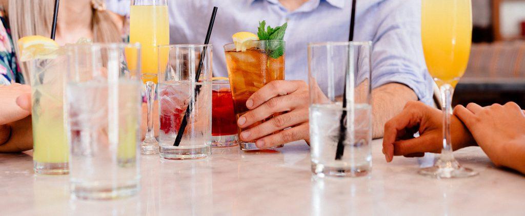 Une personne attrape l'un des cocktails posés sur une table